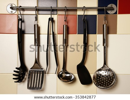 Kitchen utensils hanging on a colored  tile wall - stock photo