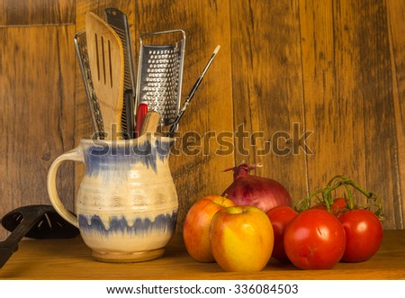 Kitchen Utensils in Stoneware pitcher against rustic wood wall surrounded by fruit and vegetables. - stock photo