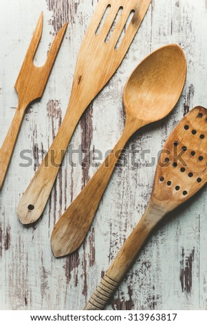 Kitchen utensils made of wood on a wooden background - stock photo
