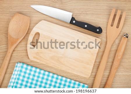 Kitchen utensils on wooden table - stock photo