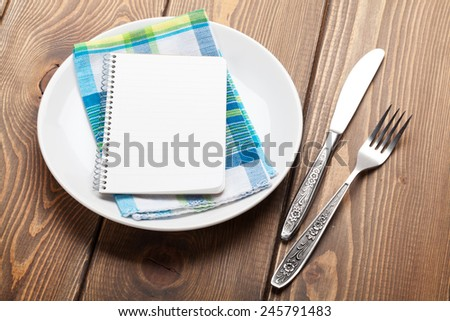 Kitchen utensils over wooden table background with notepad for copy space - stock photo
