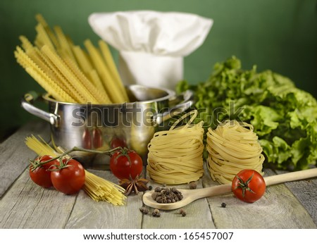 Kitchen ware with food ingredients and Chef's toque on the wooden table - stock photo