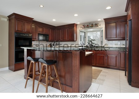 Kitchen with cherry wood cabinetry and center island  - stock photo