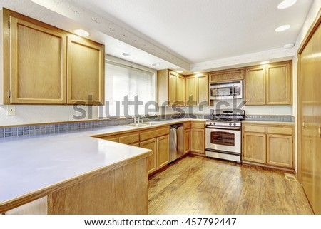Kitchen with golden wood cabinets and hardwood floor. Simple American home. Northwest, USA - stock photo