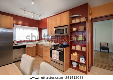 Kitchen with light wooden cabinets, breakfast table and chairs with dark red, mustard wall paint.  - stock photo