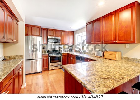 Kitchen with nice counters and stained cabinets. - stock photo