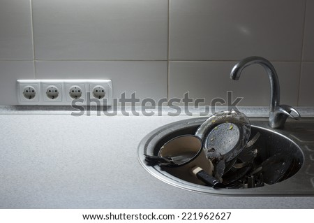 Kitchen with piles of dirty dishes - stock photo