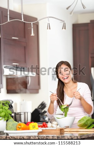 Kitchen woman making salad happy. Eat healthy concept image with beautiful blissful mixed race Asian Chinese / Caucasian female model. - stock photo