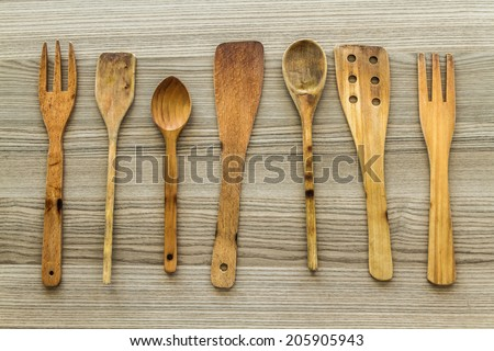 Kitchen wooden utensil of scapula, spoon and fork on wooden table - stock photo
