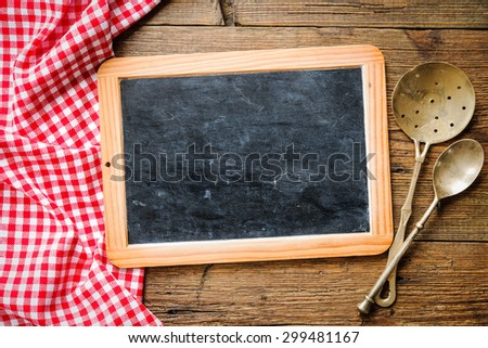 Kitchenware on a blackboard with a red checkered tablecloth - stock photo