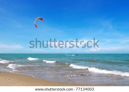Kite-boarder surfing in the blue sea over the blue sky - stock photo
