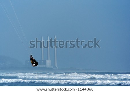 Kite surfer ( kite boarder ) jumping high above the waves with a power plant in the background, near Cayucos, California - stock photo