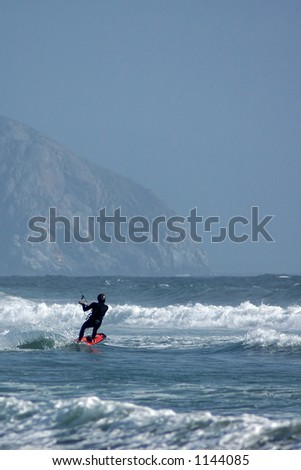 Kite surfer ( kite boarder ) riding the waves with Morro Rock in the background near Cayucos, California. - stock photo