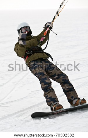 Kite surfer on snowboard in the snow - stock photo