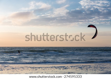 Kite surfing in the evening along the Dutch coast - stock photo