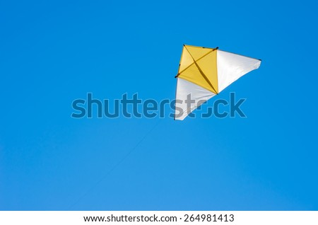 Kite triangular yellow - white, Flying high in the clear blue sky. - stock photo