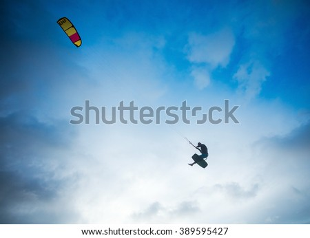 Kiteboarder performing a jump against sky - stock photo