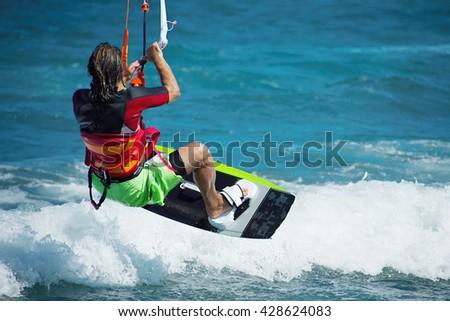 Kitesurfer flying over the wave.Kitesurfing in blue sea - stock photo