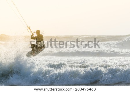 Kitesurfer jumping on a beautiful background of spray during the sunset. - stock photo