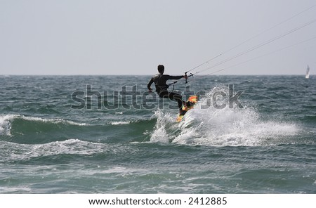 kitesurfer with a sail boat in the background - stock photo