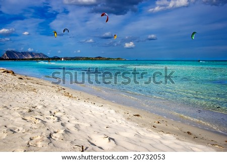 Kitesurfers gliding at high speed around the beach Cinta, Sardinia - stock photo