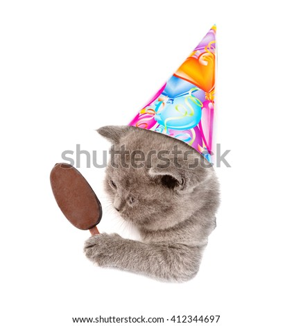 Kitten in birthday hat holding ice lolly peeking out of a hole in a paper. isolated on white background - stock photo