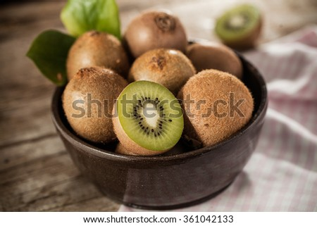 Kiwi fruit in a bowl on rustical wooden table - stock photo