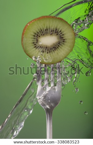 Kiwi fruit on fork with water splash and color background, concept photo. Ideal for healthy eating campaign or fitness poster. - stock photo
