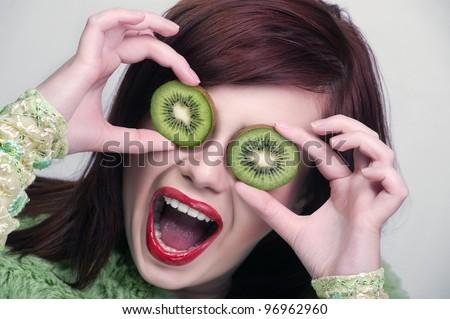 Kiwi. Healthy fruit funny woman holding kiwi fruit for her eyes. - stock photo