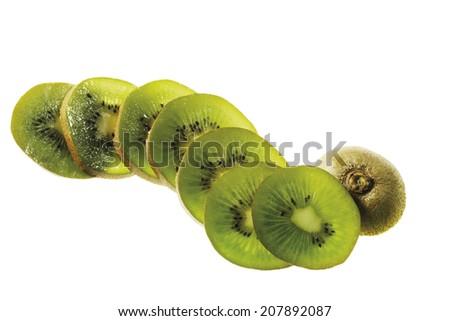 Kiwi slices in a row, whole fruit - stock photo