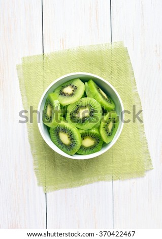 Kiwi slices in bowl over white wooden background, top view - stock photo