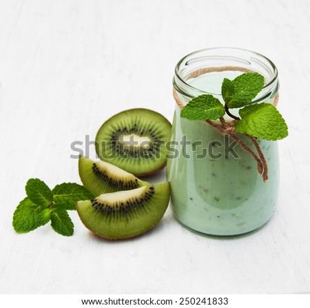 kiwi smoothie in glass on a old white wooden background - stock photo