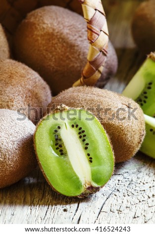 Kiwifruit poured out of a wicker basket, vintage wooden background, selective focus - stock photo