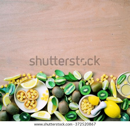 kiwis and lemons, the lemon detox water and sugar on wooden background with space for text - stock photo