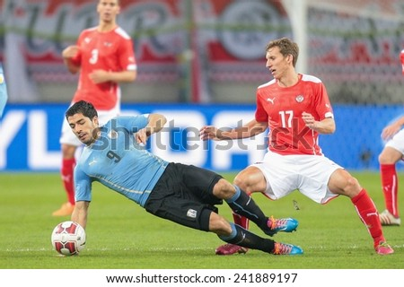 KLAGENFURT, AUSTRIA - MARCH 05, 2014: Florian Klein (#17 Austria) and Luis Suarez (#9 Uruguay) fight for the ball in a friendly soccer game between Austria and Uruguay. - stock photo