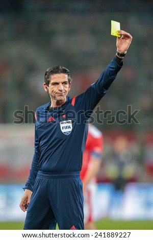 KLAGENFURT, AUSTRIA - MARCH 05, 2014: Referee Deniz Aytekin (Germany) show a yellow card in a friendly soccer game between Austria and Uruguay. - stock photo
