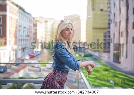 Knee figure of a young beautiful blonde caucasian girl posing leaning on a windowsill in the city wearing a jeans shirt and a floral skirt overlooking on her left - youth, freshness concept - stock photo