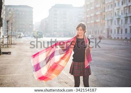 knee figure of a young pretty caucasian brown hair woman, seen from behind, posing in the street of the city, playing and dancing with her colorful scarf - carefreeness, youth, happiness concept - stock photo