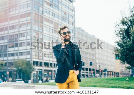 Knee figure of young handsome caucasian bearded man walking outdoor in the city, talking smart phone - communication, business, happiness concept - stock photo