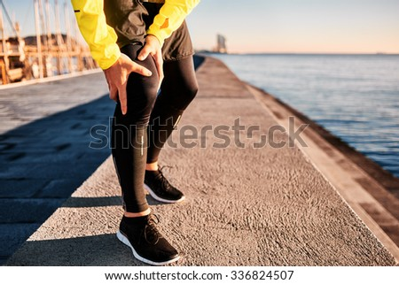 Knee Injury - sports running knee injuries on man. Close up of legs, muscle and knee outdoors. Male fitness athlete runner with pain from sprain knee