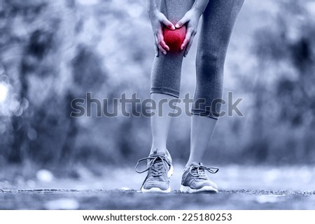 Knee Injury - sports running knee injuries on woman. Female runner with pain from sprain knee. Close up of legs, muscle and knee outdoors. - stock photo