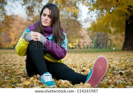 Knee injury - woman sitting in pain - stock photo