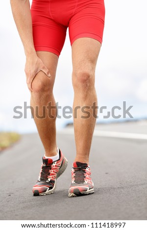 Knee pain - running sport injury. Male runner having knee problems during exercise outside. - stock photo