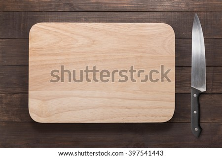 Knife and cutting board on the wooden background. - stock photo