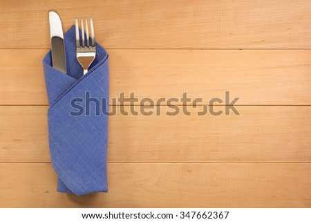 knife and fork at napkin on wooden background - stock photo