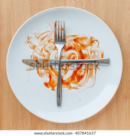Knife and fork crossed in finish plate and heart shape ketchup, concept of tasty and meaning ready for second plate. - stock photo