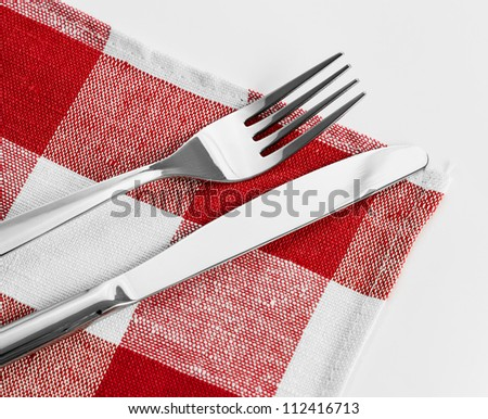 Knife and fork on red checked tablecloth - stock photo