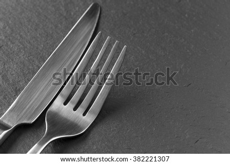 Knife and fork on slate - stock photo
