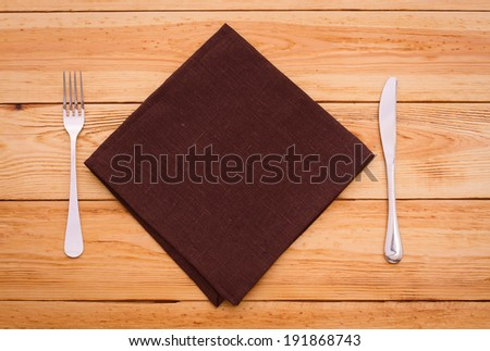 Knife and fork on wooden table with tablecloth and copyspace  - stock photo