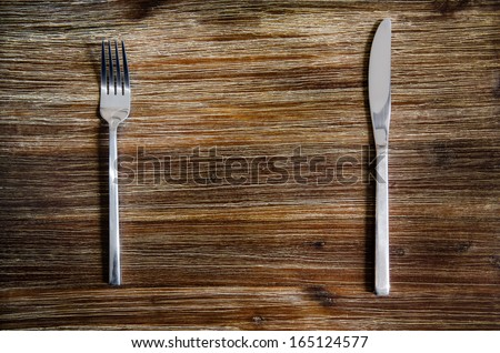 Knife and fork set on a wooden vintage table - stock photo